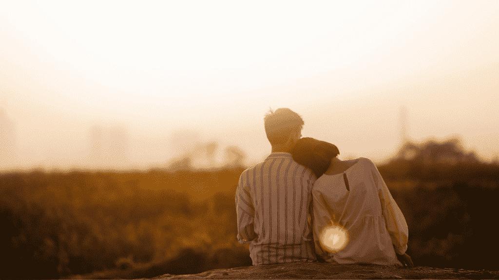Casal sentado juntos observando o por do sol