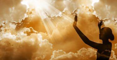 Silhueta de uma mulher com os braços exaltados ao céu.