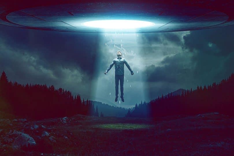 Ser extraterrestre: Ilustração gráfica de pessoa sendo abduzida por uma nave espacial, no meio de um campo.