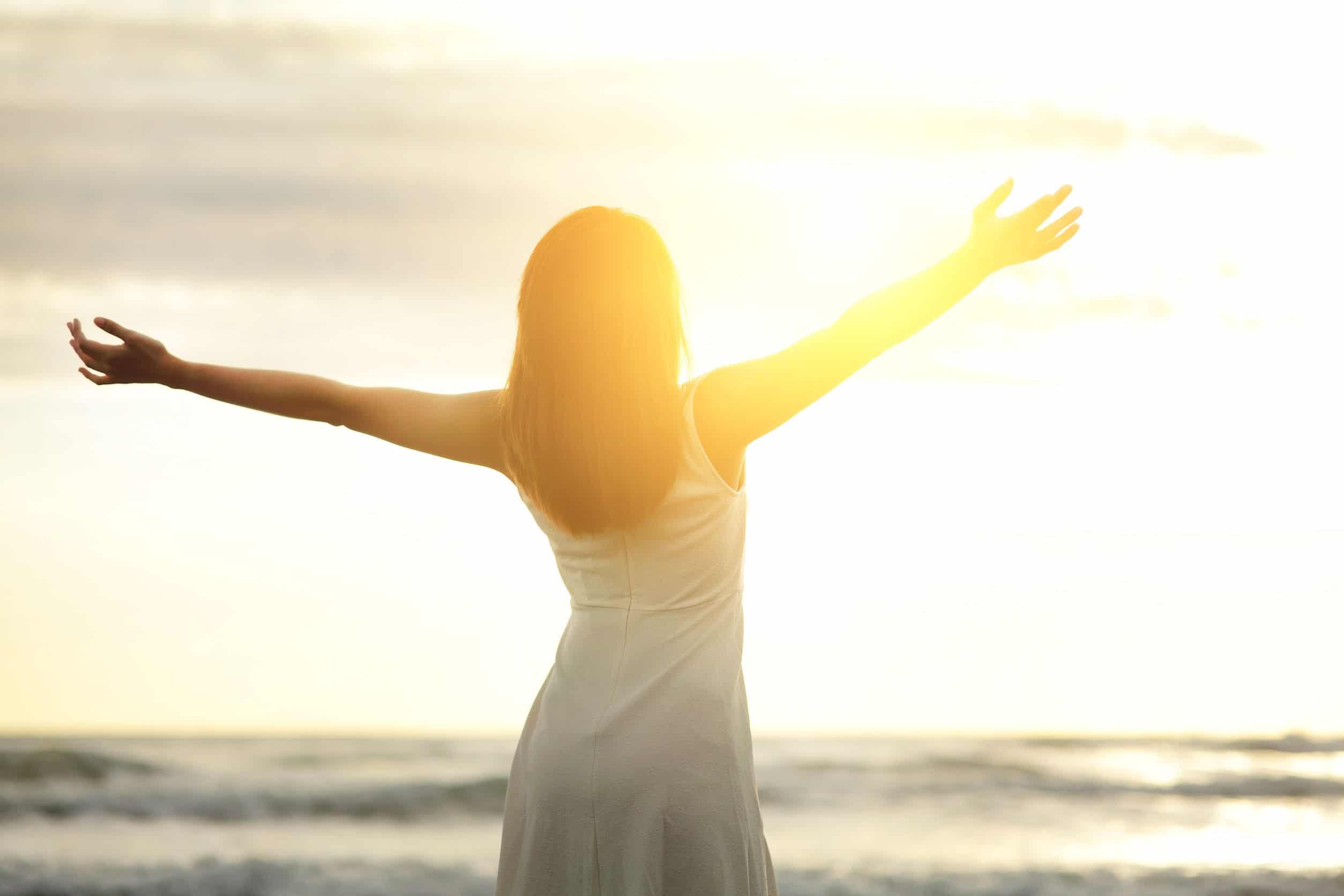 Mulher de braços abertos sob o pôr do sol.