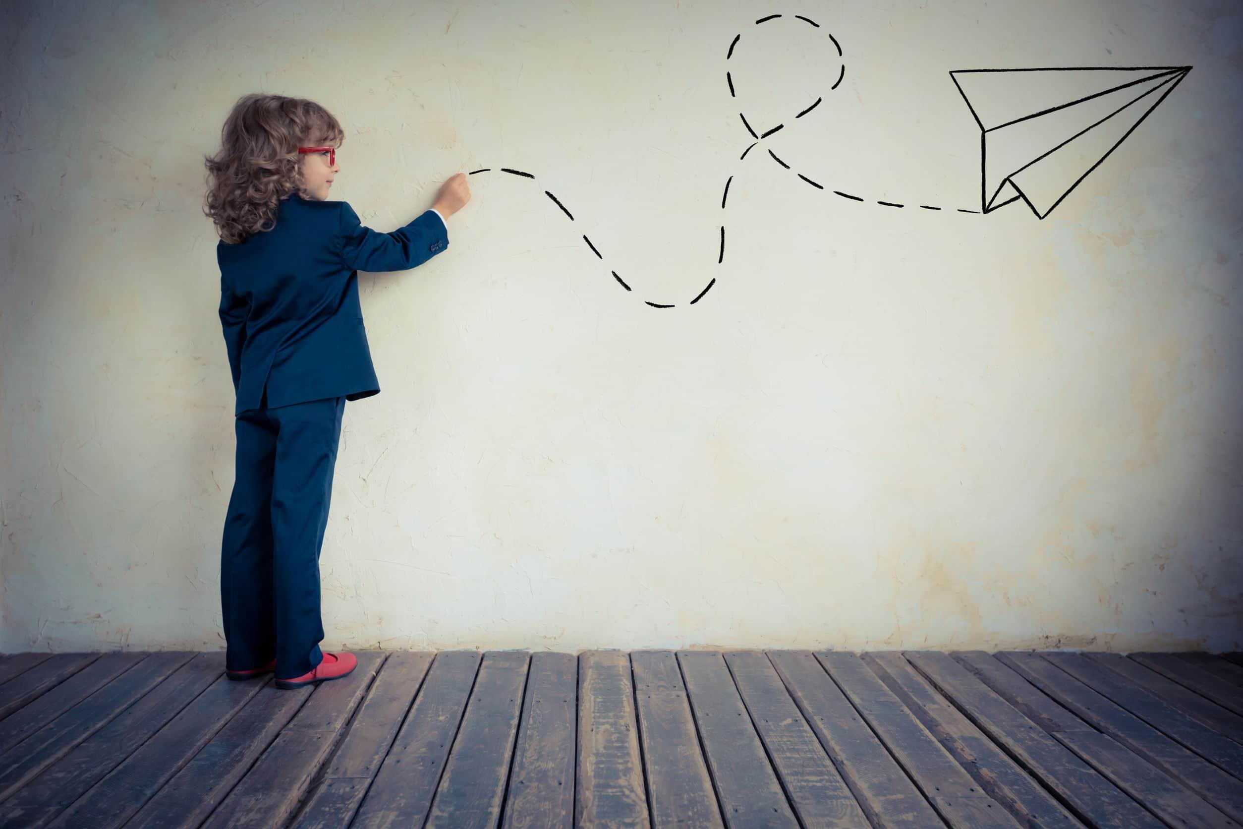 Garoto pequeno desenhando o percurso de um avião de papel na parede.