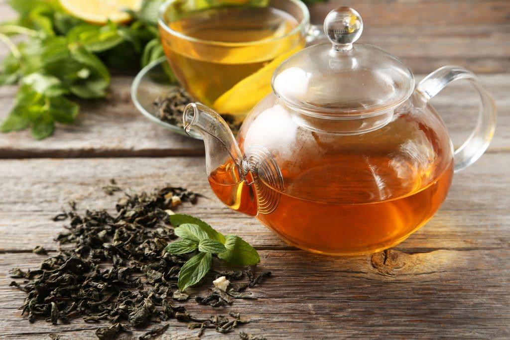 Mesa com bule de vidro com chá e folhas espalhas em volta