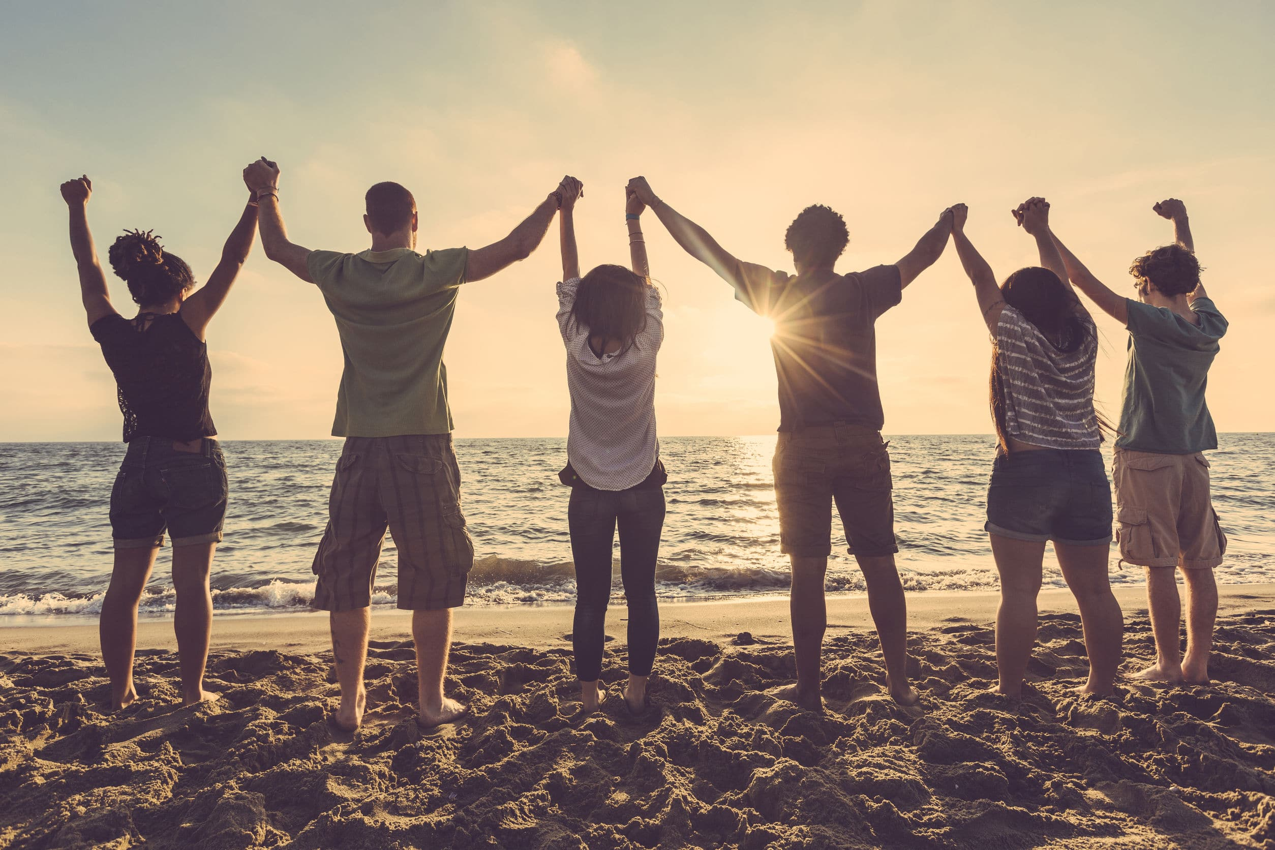 Seis pessoas na praia com as mãos dadas ao alto.
