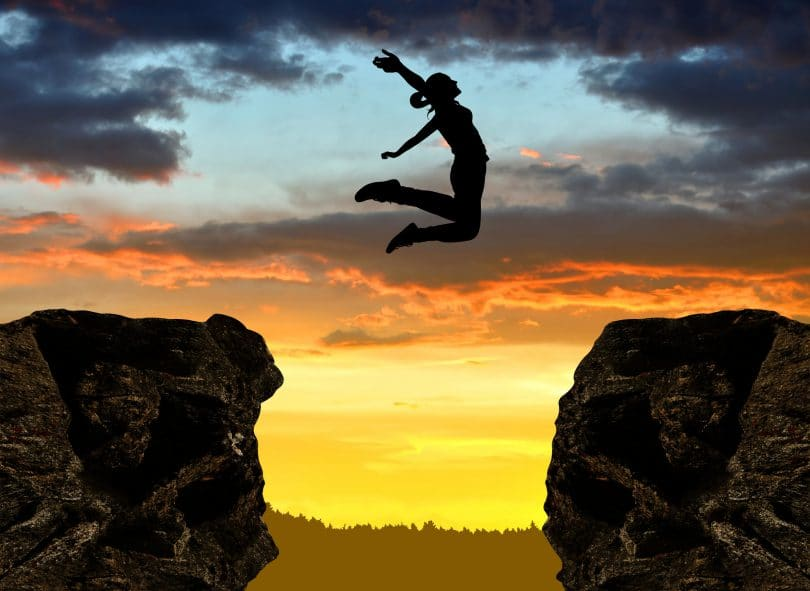 Pessoa saltando de pedra com céu de fundo