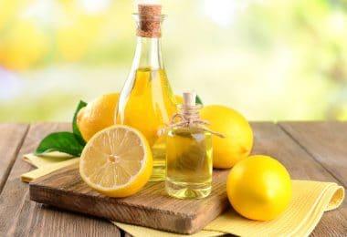 Frascos de óleo de limão ao lado das frutas.