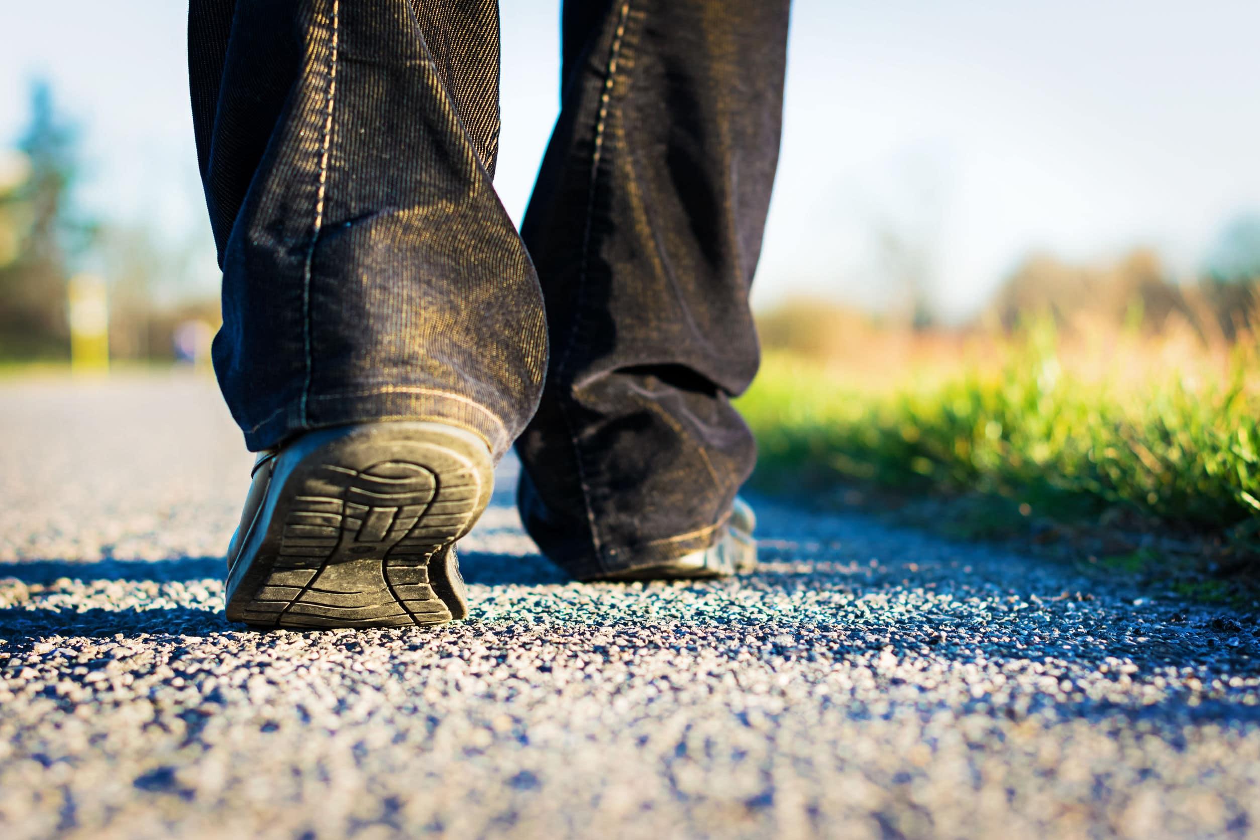 Pés com tênis andando pela estrada.