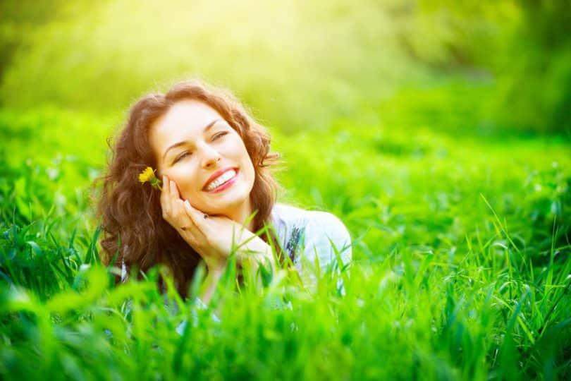 Mulher na grama com mãos o rosto sorrindo e sol refletindo
