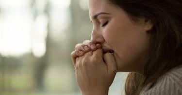 Mulher preocupada e triste com as mãos na boca prestes a chorar..