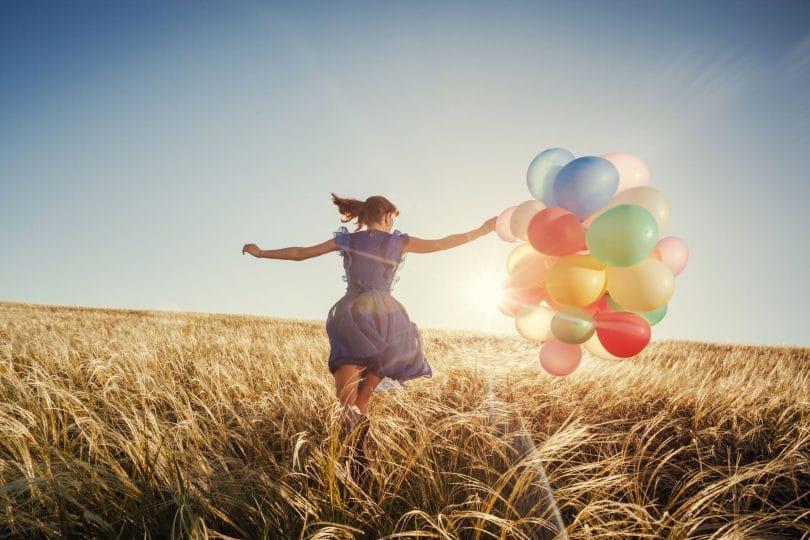 Menina correndo no campo com balões ao pôr do sol.