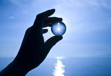 Mão segurando bola de vidro