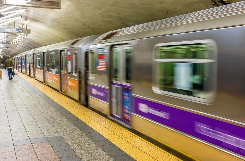 Estação de metrô em Nova York, com o trem passando em alta velocidade.