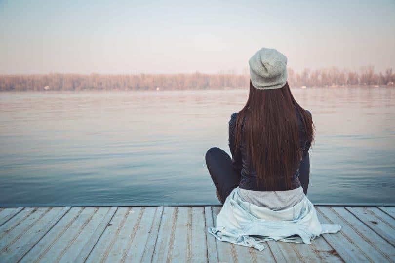 Menina jovem, sentada em um deck de madeira observando o mar.