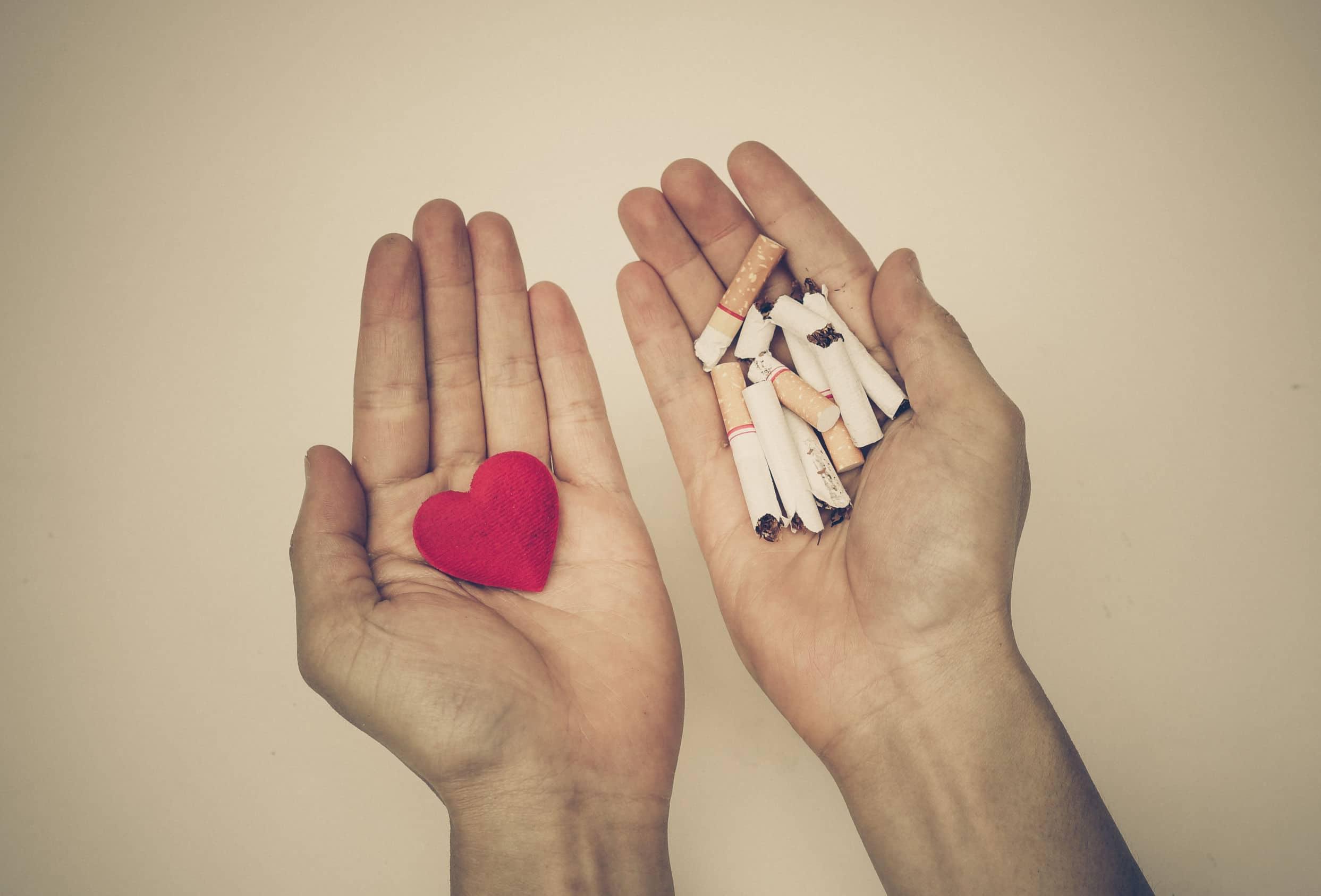 Duas mãos estendidas. De um lado tem um coração e do outro, maços de cigarros.