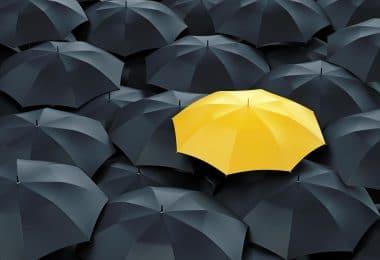Guarda-chuva amarelo ao lado de guardas-chuvas pretos.
