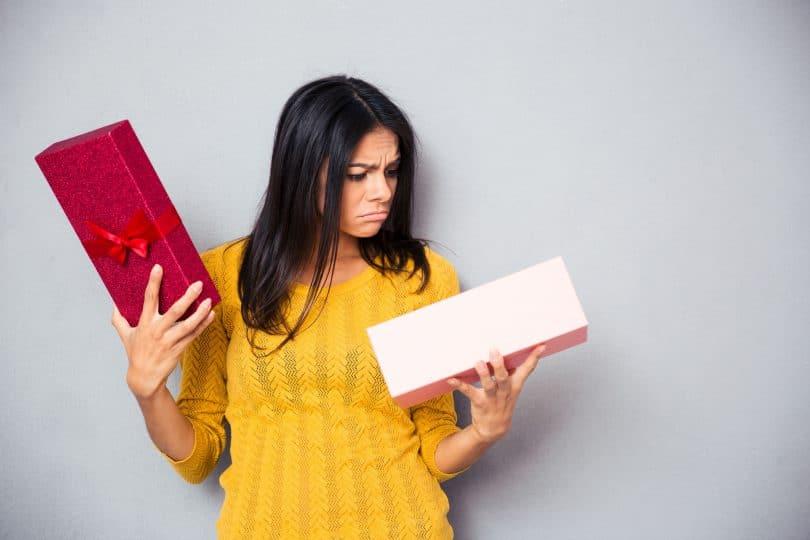 mulher infeliz segurando a caixa de presente
