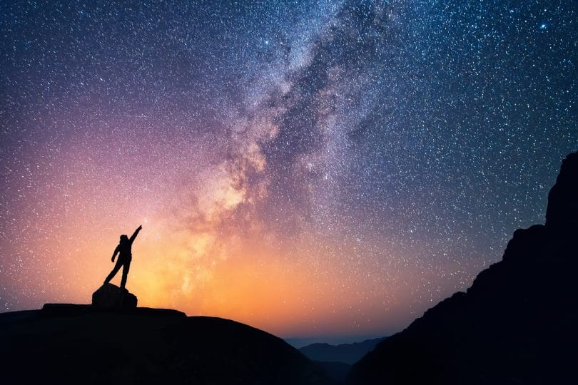 Pessoa com as mãos para o alto em noite estrelada.