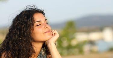 Mulher de olhos fechados iluminada pelo sol