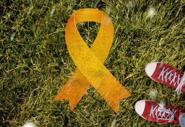 Símbolo do Setembro Amarelo sobre grama verde e um pé humano ao lado.