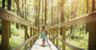Menina correndo em ponte de madeira no meio de floresta durante o dia.