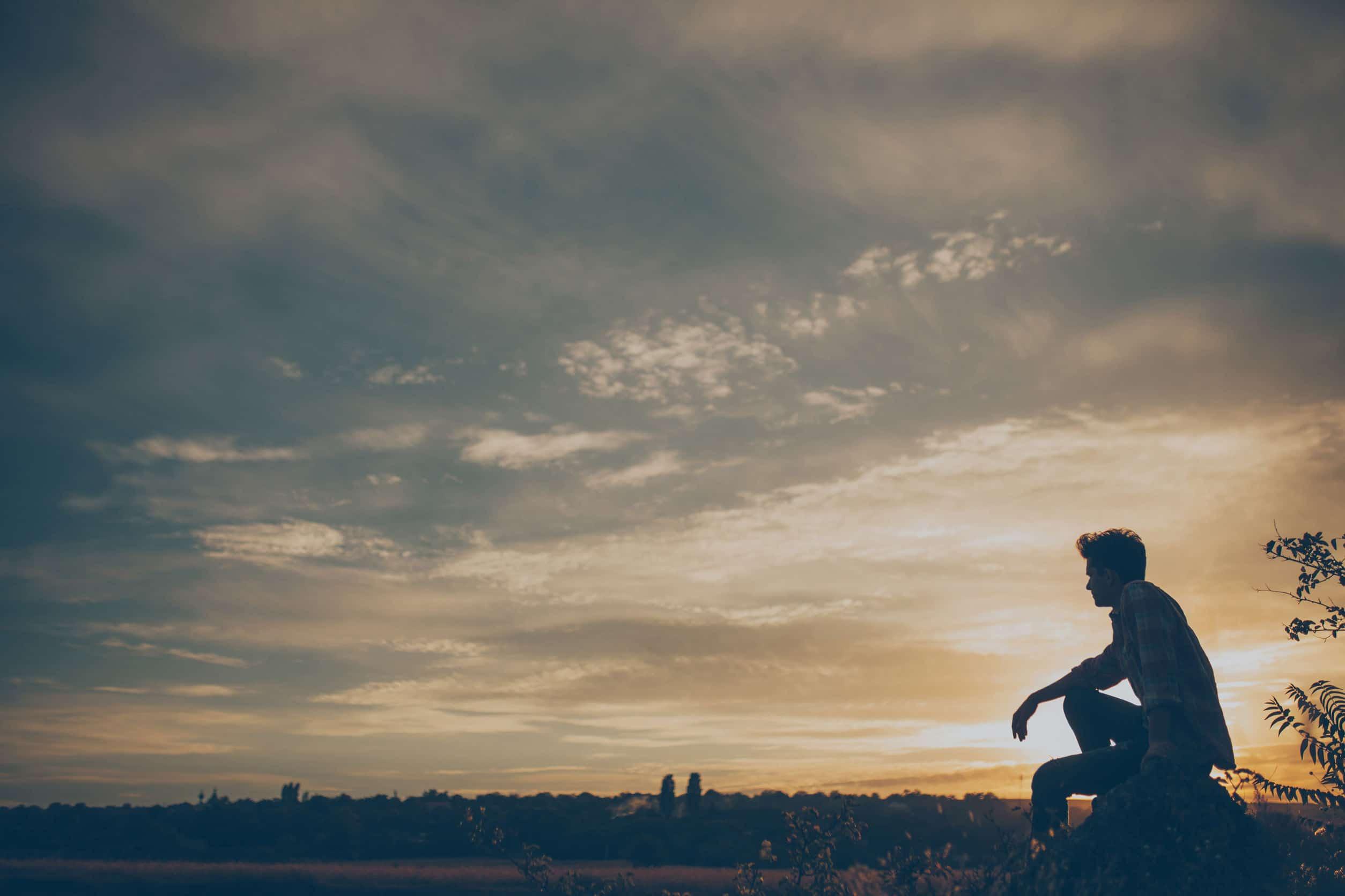 Paisagem que mostra o por do sol e um homem sentado.