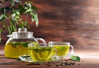 Bule de chá de ervas, feito de vidro, ao lado de outras duas xícaras de vidro cheias de chá, tudo em cima de uma mesa de madeira escura.