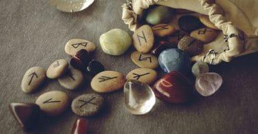Saco bege, cheio de runas, aberto em cima de uma mesa de madeira, perto de cristais.