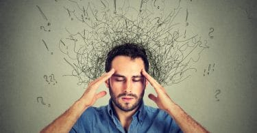Os pensamentos: Homem em pé, com as mãos na cabeça, em sinal de dor e confusão, com ilustrações gráficas de rabiscos e pontuações ao fundo.