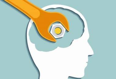Ilustração de cabeça humana com uma chave inglesa apertando um parafuso dentro do cérebro.
