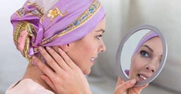 Mulher com bandana na cabeça se olhando no espelho de mão