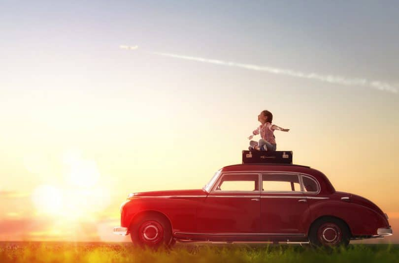 Garota sentada em cima de uma mala de viagem que está em cima de um carro vermelho.