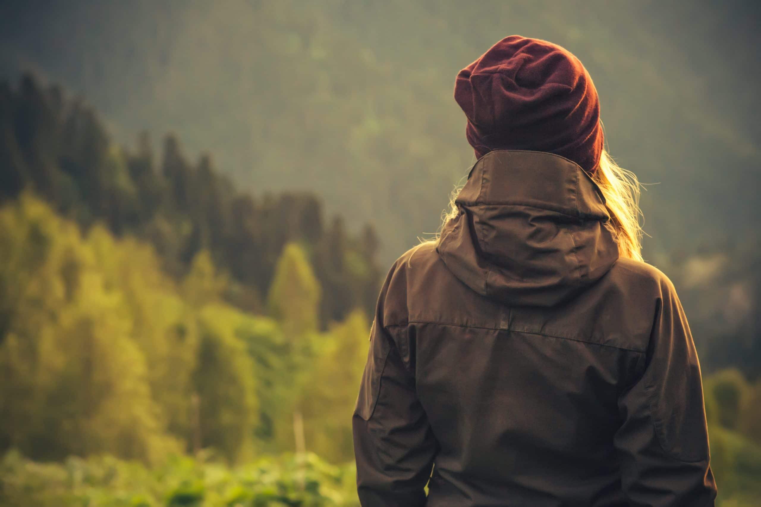 Mulher loira com roupas de frio na natureza.