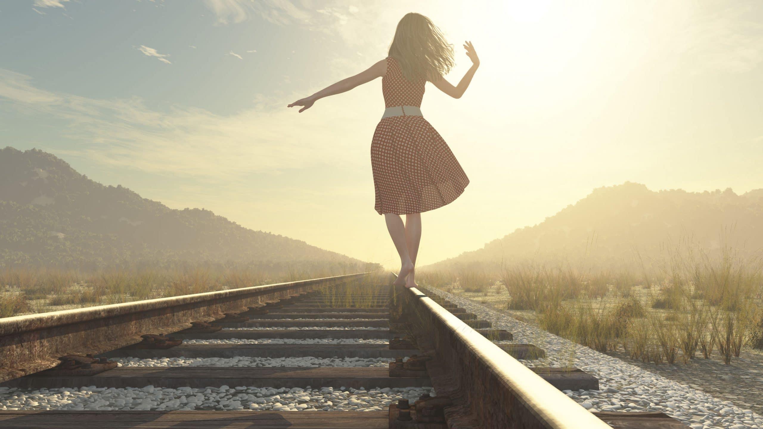 Mulher de vestido andando sobre os trilhos do trem.