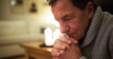 Homem rezando de olhos fechados