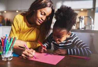 Mãe e filha desenhando em uma folha rosa.