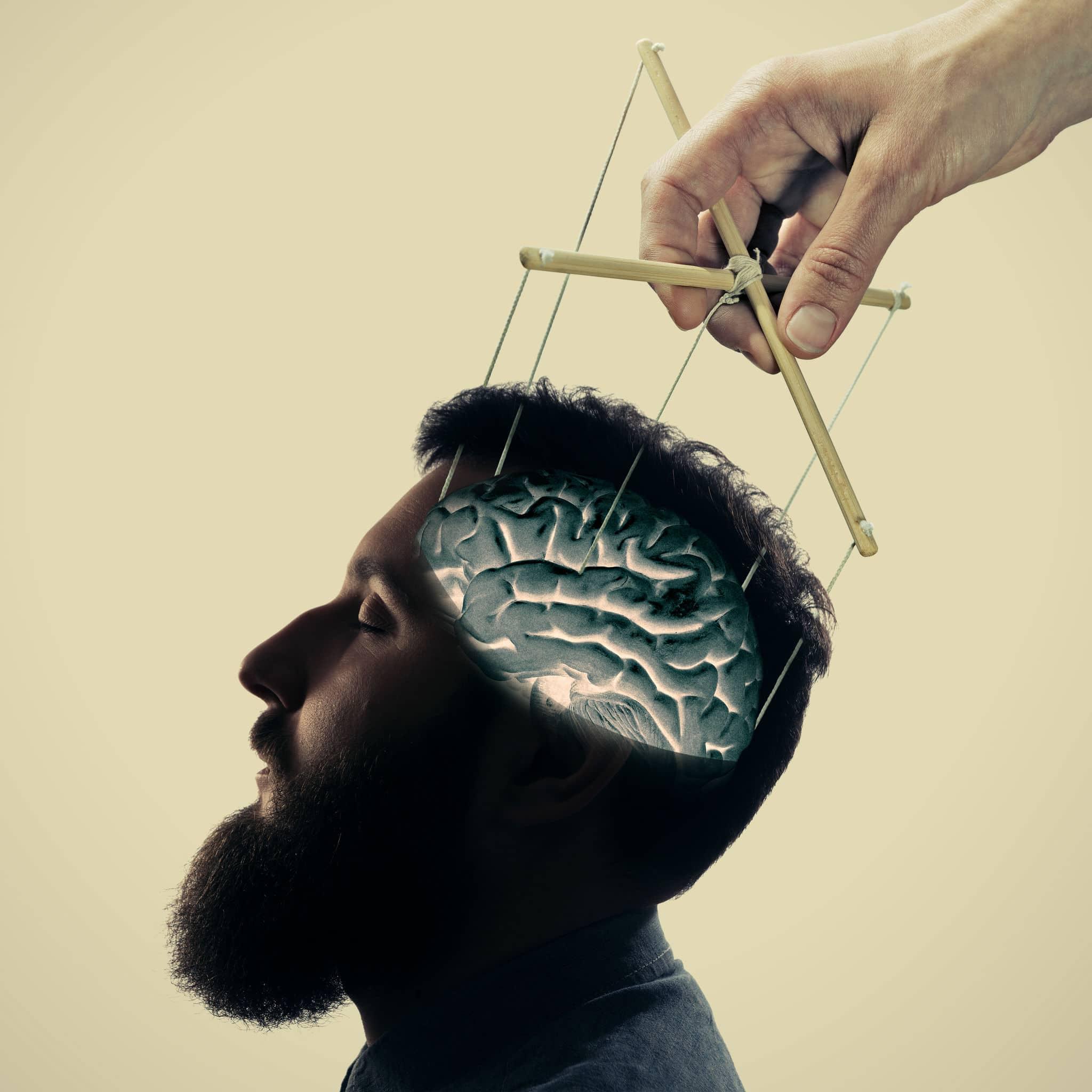 Homem barbudo com controles de marionetes sobre sua cabeça.