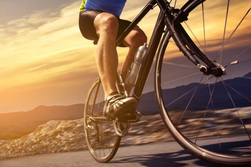 Homem andando de bicicleta por uma estrada.