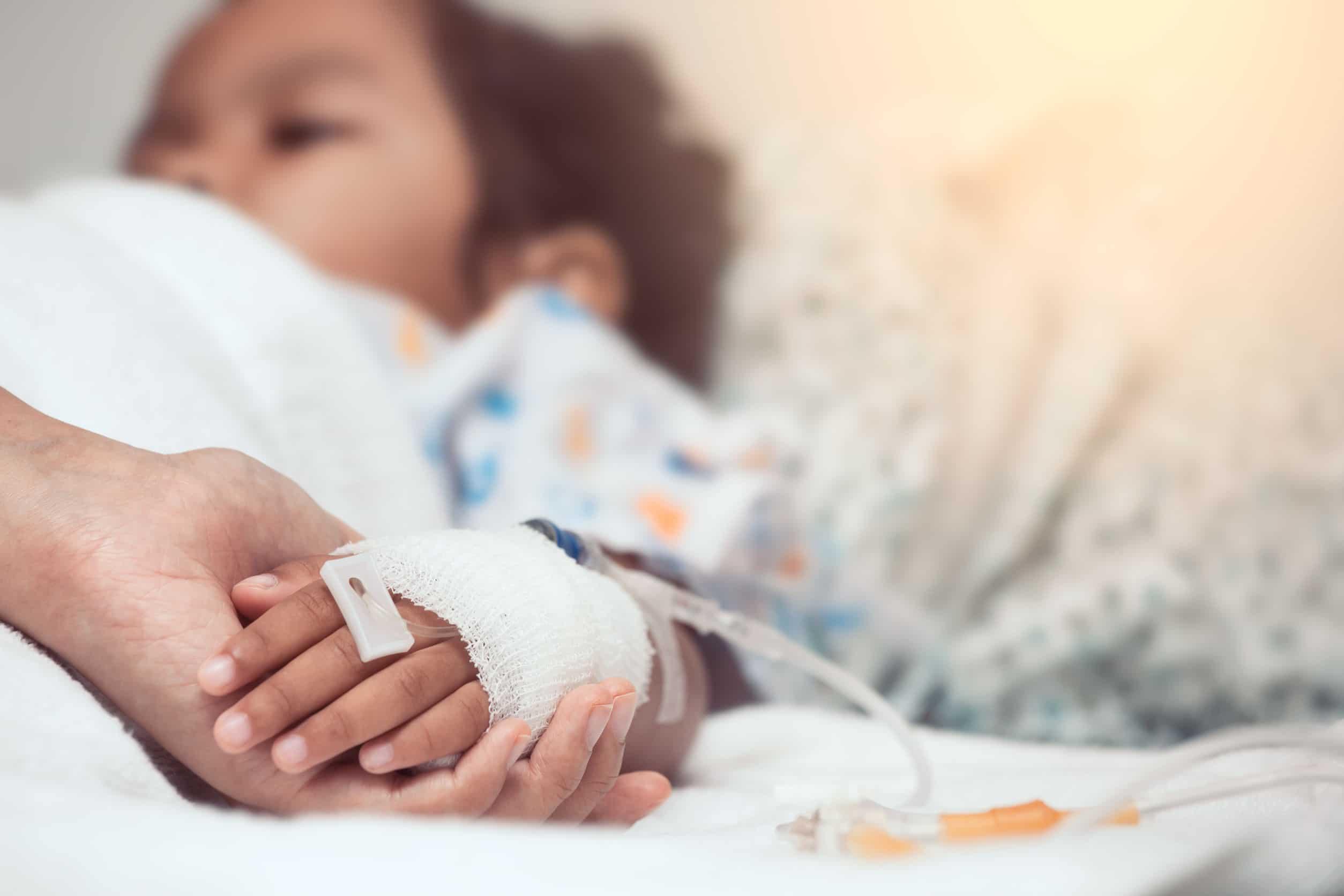 Mão adulta segurando mão de uma criança internada.