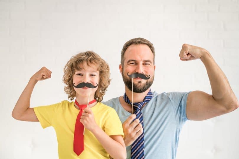 Pai e filho, ambos e brancos, segurando um bigode feito de papel em frente do rosto, dobrando o braço em sinal de força.