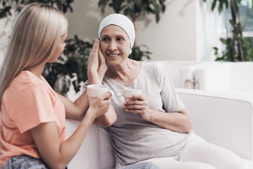 Mulher com câncer sendo acariciada.