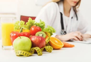 Nutricionista, trabalhando no plano de dieta com frutas e fita métrica na mesa