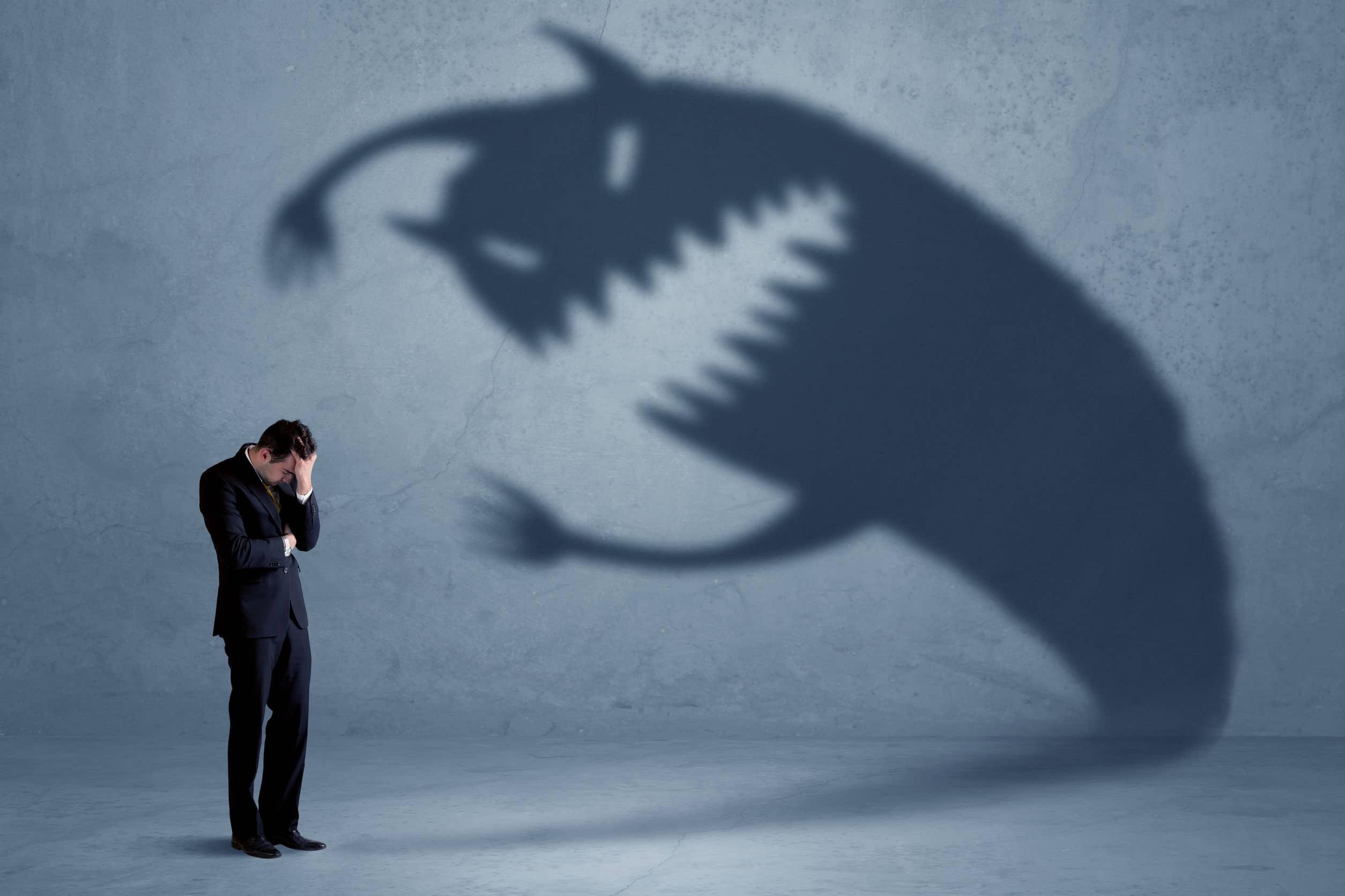 Homem com medo de uma sombra monstruosa projetada na parede.