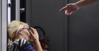 Mulher olhando para cima enquanto um homem aponta os dedos para ela.