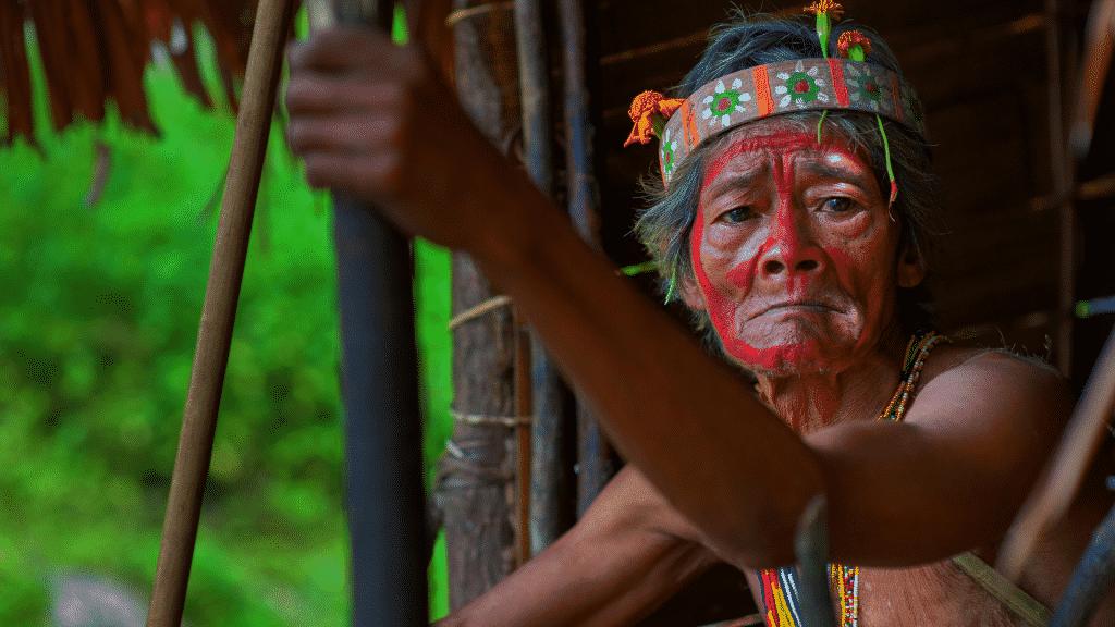 Homem indígena idoso segurando um bastão de madeira e bandana