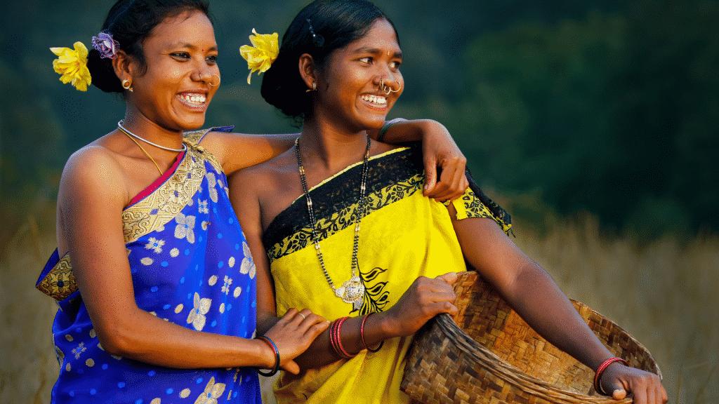 Duas mulheres indígenas sorrindo com flores no cabelo