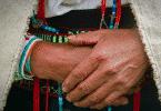 Fotografia das mãos de uma mulher indígena com pulseiras e colares em volta