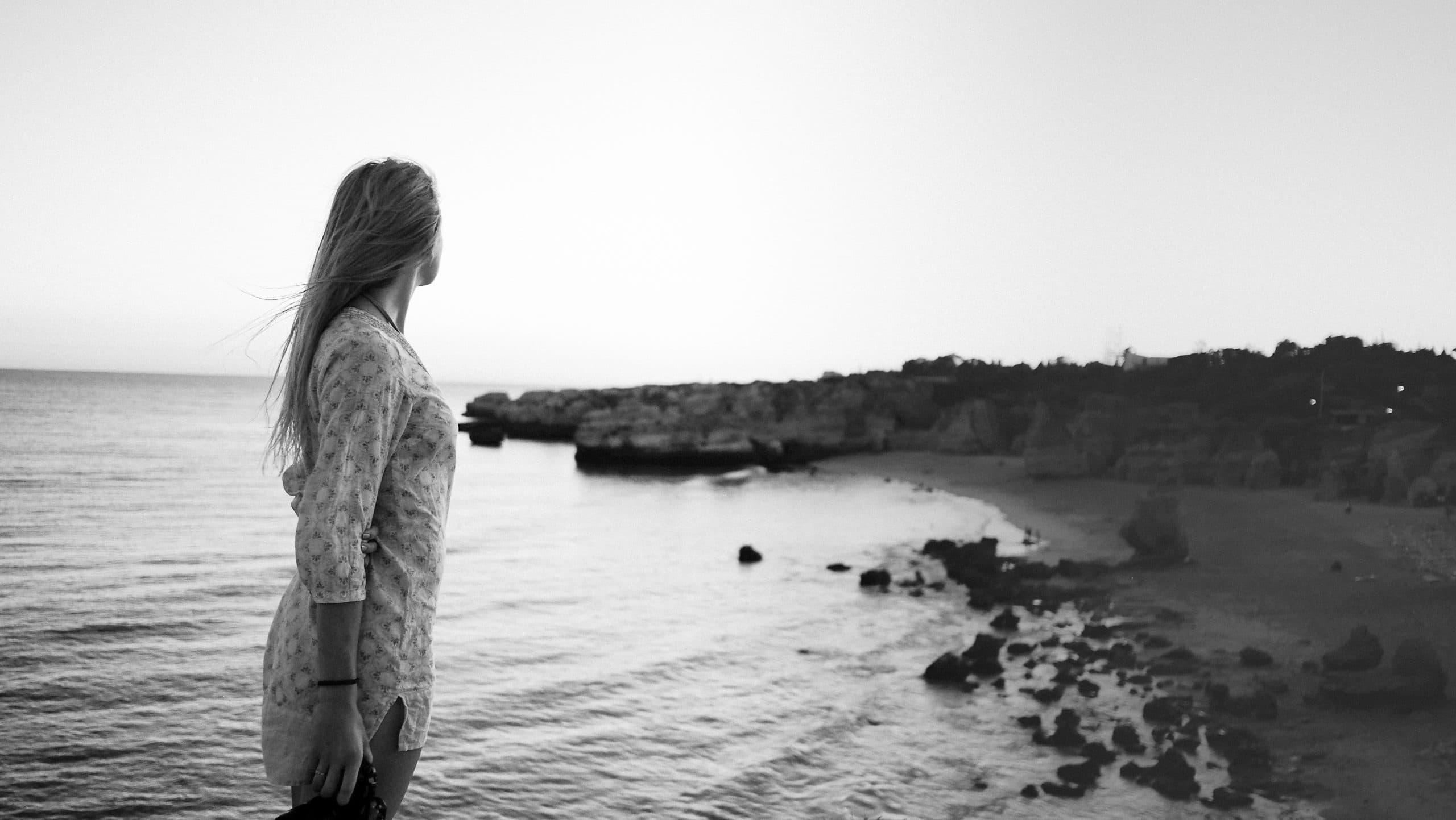 Mulher em preto e branco olhando para o mar