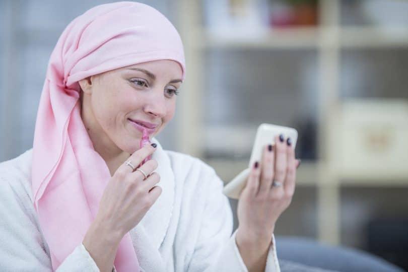 Mulher com câncer passando batom.