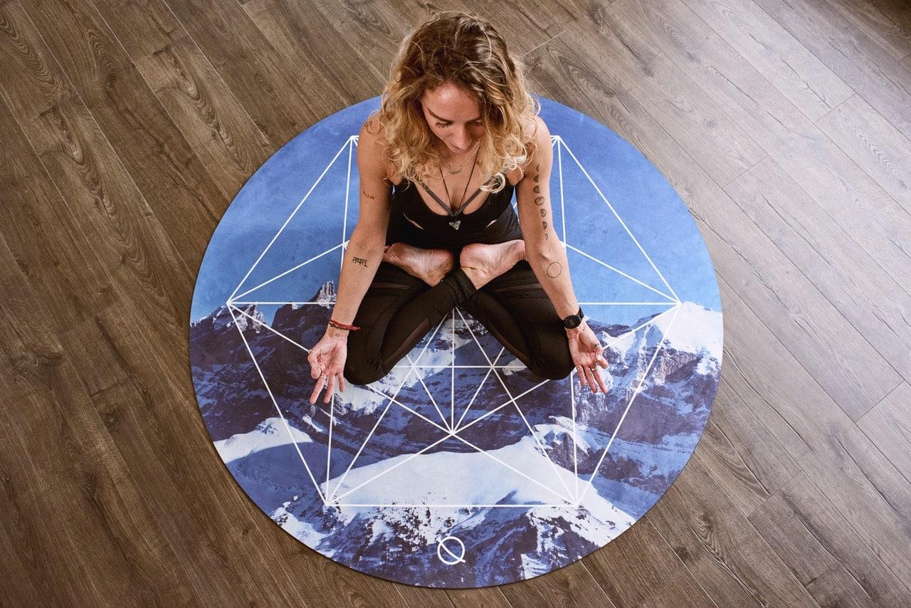 Mulher sentada em tapete meditando