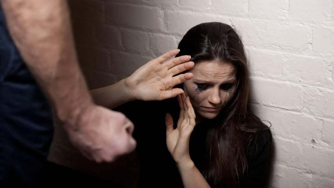 Mulher chorando abaixada reagindo às ameaças de um homem.