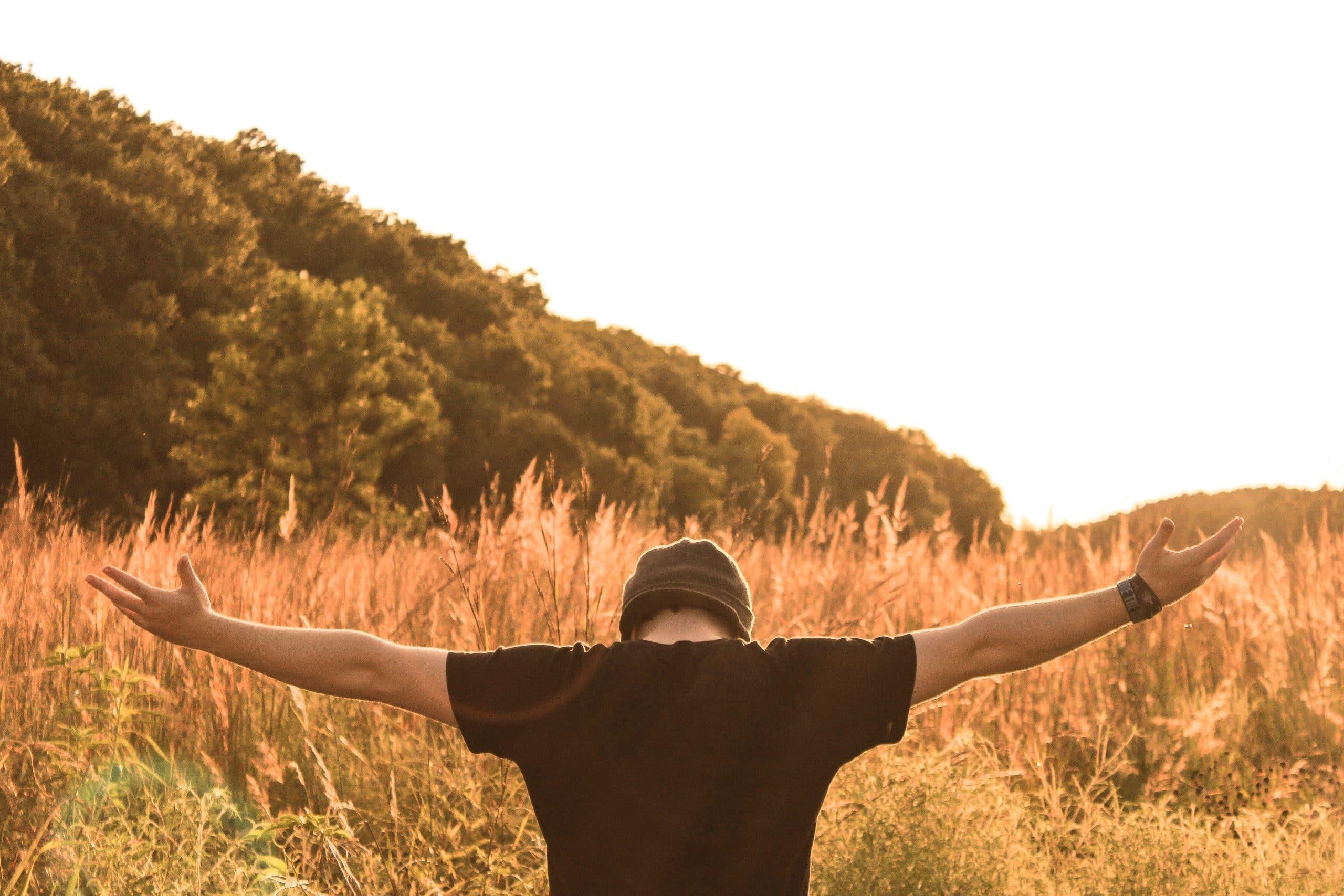 Homem de braços abertos no meio de um campo.